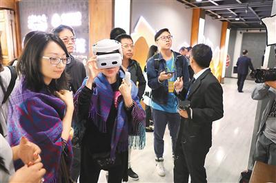 华文媒体代表在丽江的数字古城5G展馆体验景区VR直播。