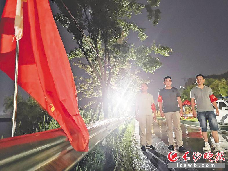 11日晚11时许,开福区秀峰街道工作人员冒雨巡查江堤。长沙晚报全媒体记者 小刘军 摄