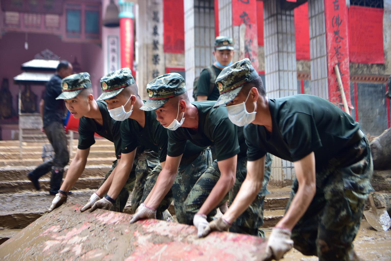武警赣州支队官兵在江西省瑞金市九堡镇菜市场合力清理淤泥(7月20日摄)。