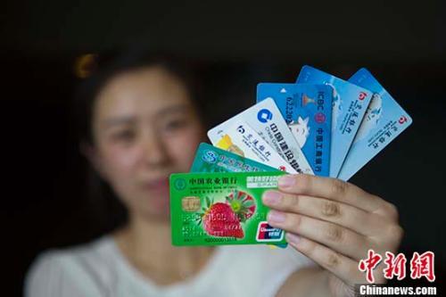 资料图:民众展示银行卡。 <a target='_blank' href='http://www.chinanews.com/'>中新社</a>记者 张云 摄