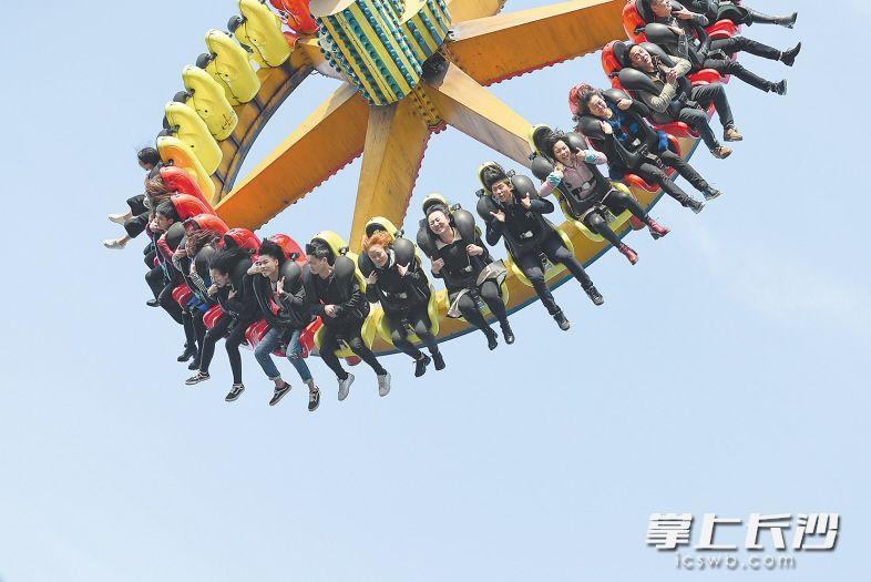 游乐场大摆锤上的游客在蓝天里尽情感受刺激。