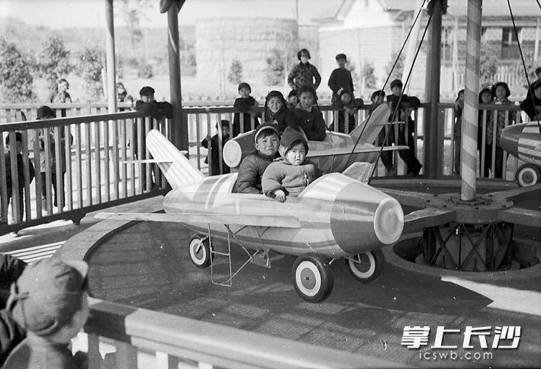 """1957年2月22日,烈士公园儿童游艺场内,新建了一个""""飞机场"""",装有4架不同颜色的""""喷气式电动飞机"""",吸引了众多小乘客。"""