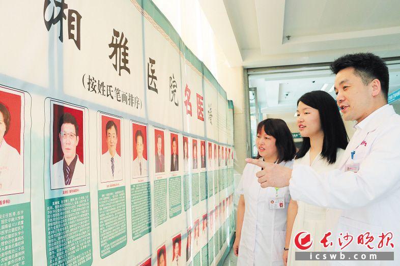 """在""""湘雅名医谱""""前,郭峰和高清平给17岁的女儿郭乐之讲名医故事,勉励她好好学医。 长沙晚报通讯员 罗闻 摄"""