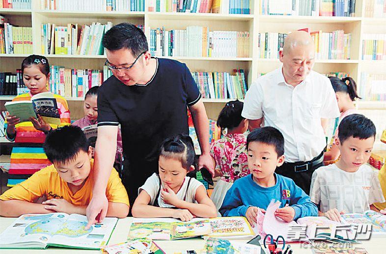 胡健老师(戴眼镜者)在公益书屋给孩子们解疑释惑。受访者供图