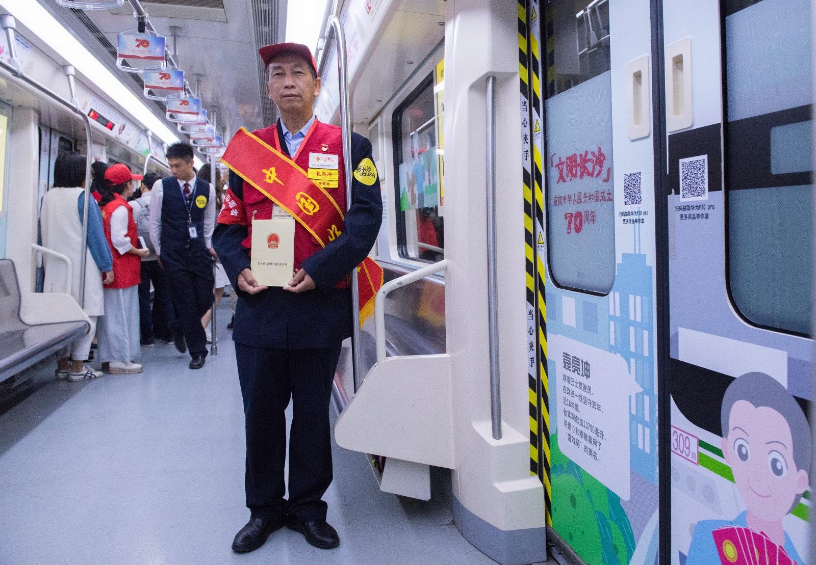 """""""热血公交哥""""袁亮坤在列车上和自己的展示栏合影。长沙晚报全媒体记者 邹麟 摄"""