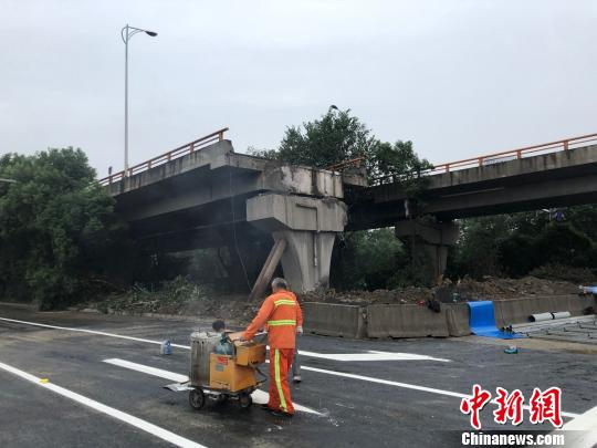 工作人员给事发路段的地面喷上白色的交通标线。 孙权 摄