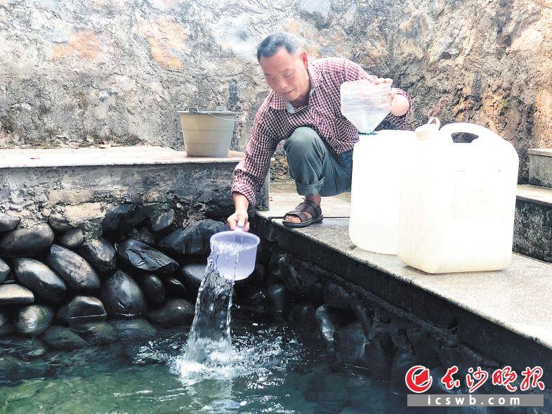 家住达浒镇象形村的村民王汉荣专程赶了几里路,来书香村打水。 长沙晚报全媒体记者 钱娟 摄