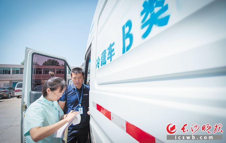 9月19日11时45分 地点:长沙县星沙街道社区卫生服务中心 收货前,接种门诊工作人员查看冷藏车内疫苗的保存温度。