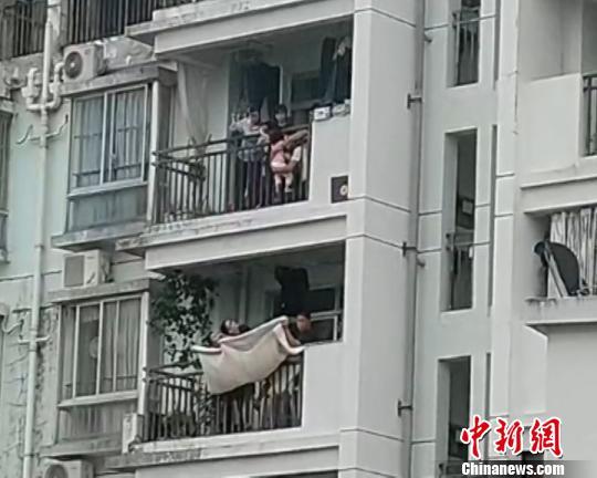 图为邻居拉被子紧急施救。 钟欣 摄