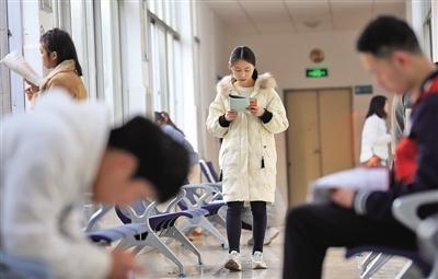 12月11日,在湖南省衡阳市南华大年夜学藏书楼走廊、过道,考研门生在看书复习。